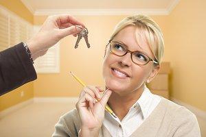 Woman in Room Being Handed Keys