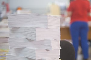 Paper stack in front of worker in the typography