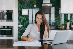 Attractive young modern business woman talking on mobile phone and working with documents and laptop in the kitchen at home