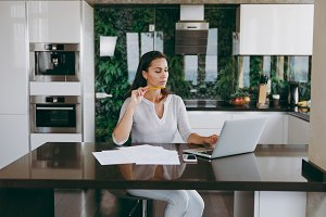 Attractive young modern business woman working with documents and laptop in the kitchen at home