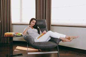 Beautiful young woman at home sitting on modern chair in front of window, relaxing in her living room and reading book