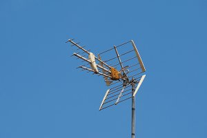 tv antenna aerial over blue sky with copy space