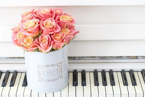 pink roses in a round box on piano