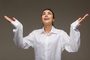 Beautiful girl in a white shirt shows emotions - hope. On a light background.