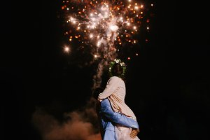 Wedding fireworks. Bride and groom hugging