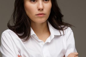 Beautiful girl in a white shirt shows emotions - disorder. On a light background.