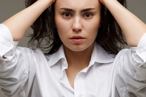 Beautiful girl in a white shirt shows emotions - thoughtfulness. On a light background.