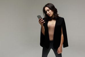 Beautiful fashionable woman in in jeans and a jacket. with phone in hands