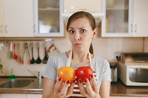 A young confused woman in an apron decides to choose a red or yellow tomato in the kitchen. Dieting concept. Healthy lifestyle. Cooking at home. Prepare food.