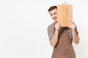 Young confident man chef or waiter in striped brown apron, shirt holding wooden cutting board, knife isolated on white background. Male housekeeper or houseworker. Domestic worker for advertisement.