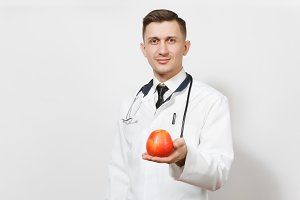 Smiling handsome young doctor man isolated on white background. Male doctor in medical uniform stethoscope holding red apple. Healthcare personnel health medicine concept. Proper nutrition. Copy space