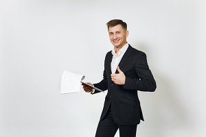Young successful handsome rich business man in black suit working with documents tablet isolated on white background for advertising. Concept of money, achievement, career and wealth in 25-30 years.