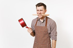Aggressive man chef or waiter in striped brown apron, shirt holding red empty stewpan, wooden spoon in mouth isolated on white background. Male housekeeper or houseworker. Kitchenware, cuisine concept