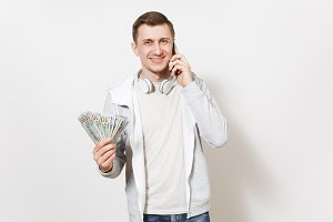 Young handsome smiling man in t-shirt, light sweatshirt with headphones around neck talking on mobile phone with bundle of dollars, cash money in hand isolated on white background. Concept of success.
