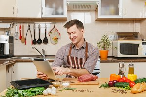 Young man in apron sitting at table with vegetables, looking for recipe in tablet, cooking at home preparing meat stake from beef, in light kitchen with wooden surface, full of fancy kitchenware.
