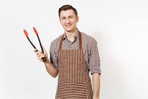 Young man chef in striped brown apron, shirt holding black kitchen serving plastic pair of tongs for salad isolated on white background. Male housekeeper or houseworker. Kitchenware, cuisine concept.