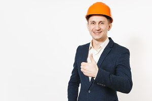 Young handsome successful smiling businessman in dark suit, protective construction helmet showing thumb up isolated on white background. Male worker for advertisement. Business, working concept.