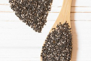 Heart and chia seeds in wooden spoon on white background. Healthy food