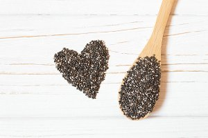 Heart and chia seeds in wooden spoon on white background