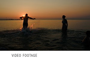 Family bathing in the sea at sunset