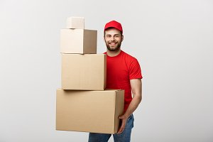 Delivery Concept: Handsome delivery man hold pile cardboard boxes on grey background.