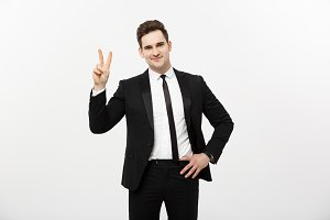 Happy businessman showing two fingers or victory gesture, against grey background. Success in business, job and education concept. Blank copyspace area for advertisiment, slogan or text