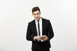 Checking statistics. Successful and confident businessman stands and checks online news on the tablet inside business center. Young business in formal suit.