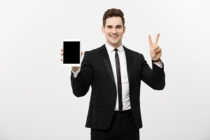 Happy businessman showing two fingers or victory gesture holding tablet, against grey background. Success in business, job and education concept. Blank copyspace area for advertisiment, slogan or text
