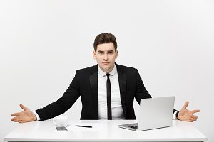 Business Concept: Young businessman working in bright office, sitting at desk, using laptop with serious facial expression