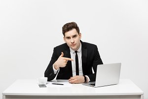 businessman sitting at desk point finger at isolated laptop screen , handsome young business man looking at camera, over white background