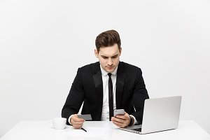 Business Concept: Portrait of young businessman using laptop computer and mobile phone holding debit card. Isolated over grey background.