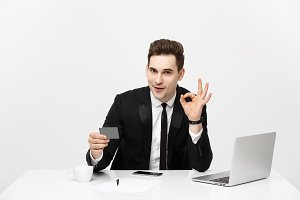 Caucasian office man in formal suit and tie demonstrating digital money in plastic credit card and showing ok isolated over gray background.