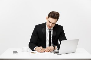 Business Concept: Portrait concentrated young successful businessman writing documents at bright office desk.