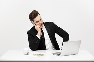 Business Concept: Portrait young successful businessman working in bright office, using laptop, talking on phone.