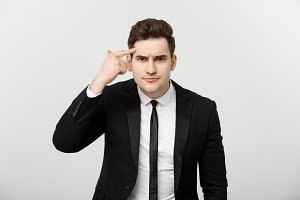 Business man points his finger at his head and thinking isolated on a gray background