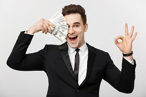 Business Concept: Confident young businessman holding money and showing ok sign over white grey background.