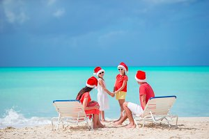 Happy family of four on beach in red Santa hats