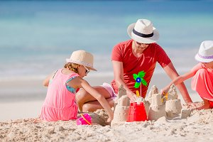 Father and two girls playing with sand on tropical beach
