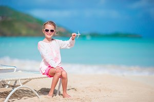 Happy little girl with toy airplane in hands on white sandy beach.