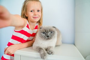 Cute little girl kissing her pet cat at home. Love between kid and pet