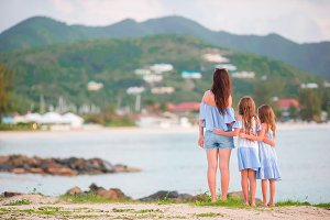 Adorable little girls and young mother on white beach