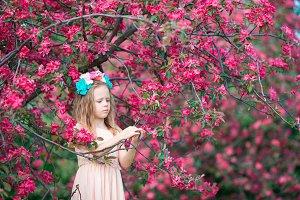 Little beautiful girl enjoying smell in a flowering spring garden