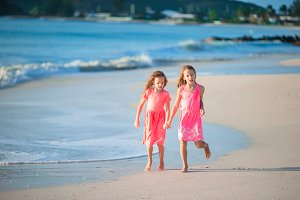 Little beautiful girls walking on tropical seashore