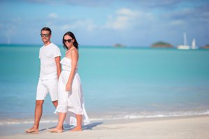 Young couple walking on tropical Carlisle bay beach with white sand and turquoise ocean water at Antigua island