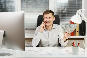 Handsome smiling business man in shirt sitting at the desk talking on mobile phone with lot of cash money, working at computer with modern monitor, lamp, documents in light office. Manager or worker.