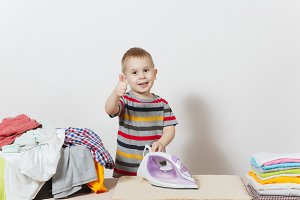 Happy little boy show thumb up, ironing family clothing on board with iron. Kid helping with housework isolated on white background. Encouraging Autonomy in children concept. Copy space advertisement.