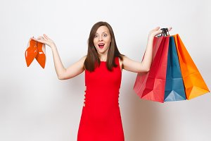 Attractive impressive glamour caucasian fashionable young brown-hair woman in red dress holding beige shoes with red sole, multi colored packets with purchases, shopping isolated on white background.