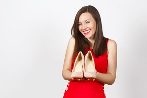 Pretty glamour caucasian fashionable young brown-hair woman in red dress holding beige shoes with red sole of her shopping on palms of hands isolated on white background. Copy space for advertisement.