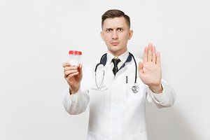 Doctor man showing stop gesture with palm isolated on white background. Male doctor in medical uniform, stethoscope holding bottle with white pills. Healthcare personnel, health, medicine concept.