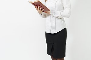 Full length of beautiful European young smiling brown-hair woman in white shirt, black skirt, glasses reading book isolated on white background. Manager, worker, student. Copy space for advertisement.